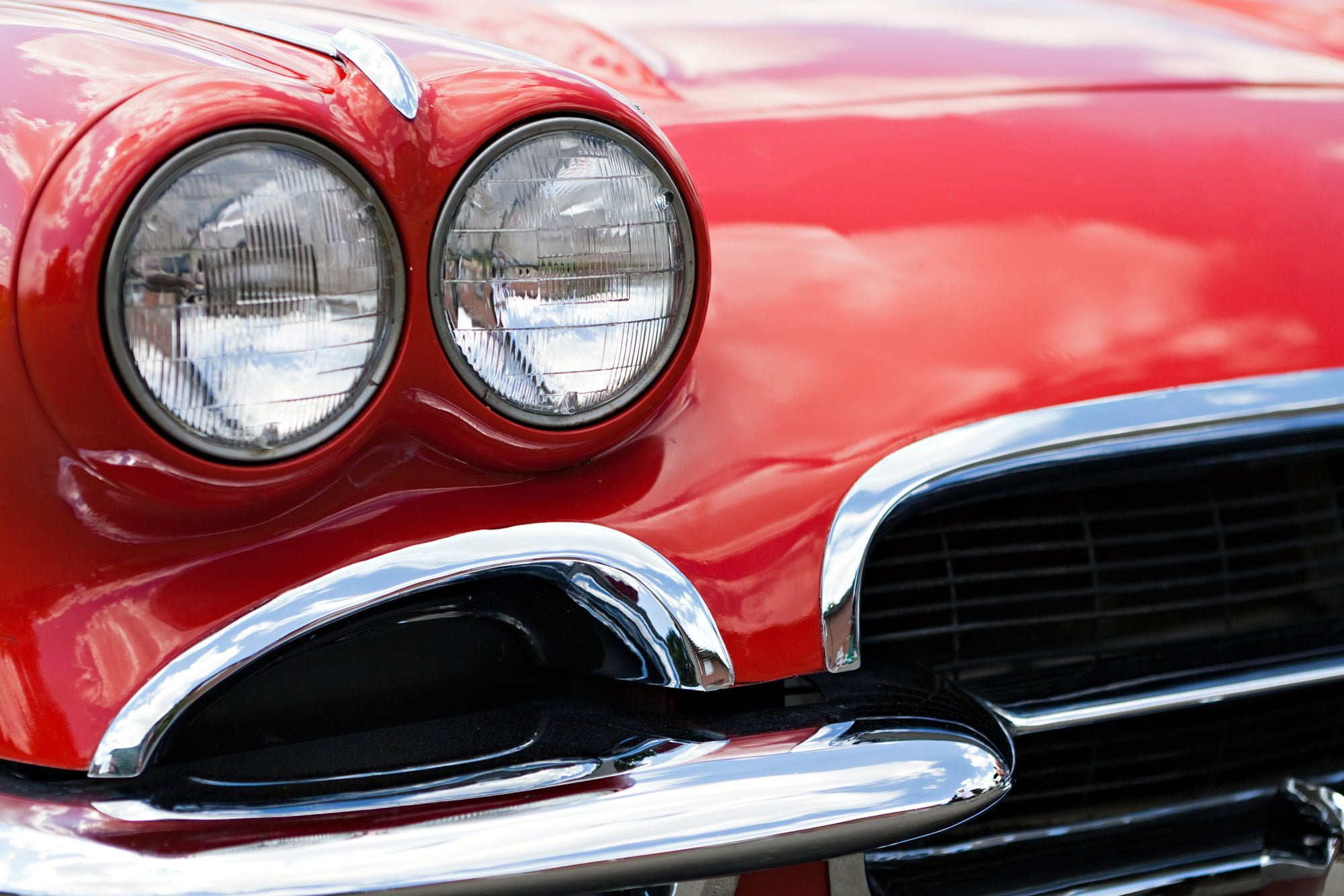 Closeup image of the front of a sparkling clean classic red car
